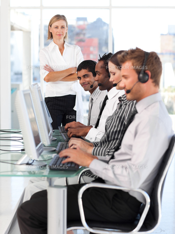 Confident female leader managingher team in a call center FYI00482828
