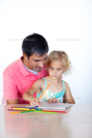 Radiant father drawing with his daughter FYI00482842