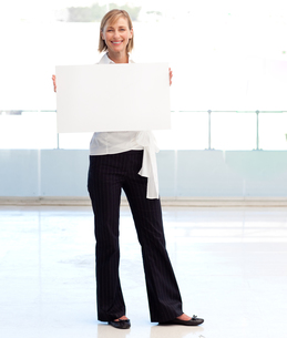 Businesswoman holding a white  card FYI00482859
