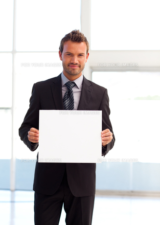 Friendly businessman holding a white card FYI00482861