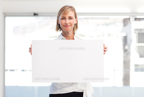 Mature woman showing a big business card FYI00482866
