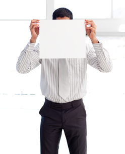 Businessman showing a white card covering his face FYI00482871