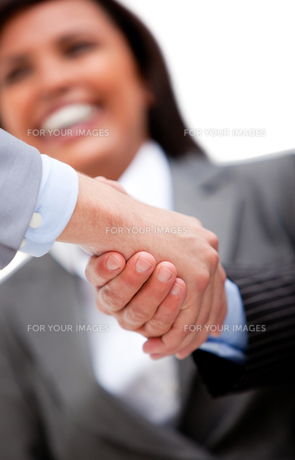 Smiling businesswoman looking at her partners shaking hands FYI00482876