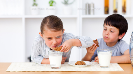 Happy brother and sister eating biscuits and drinking milk FYI00482912