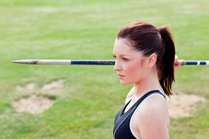 Concentrated athletic woman ready to throw the javelin FYI00483202