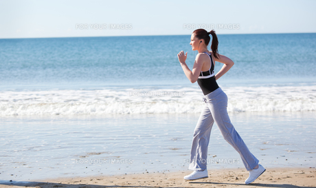 Beautifull woman running on the beach FYI00483209