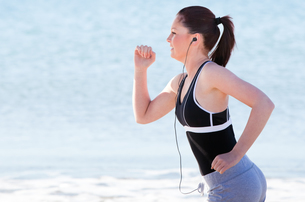 Young woman running on the beach listening music FYI00483235