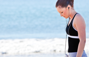 Athletic woman listening music on the beach FYI00483237