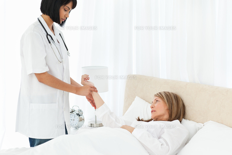 Nurse taking the pulse of her patient FYI00483454