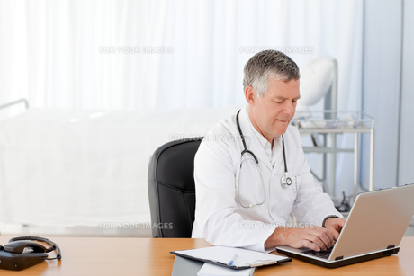 A senior doctor working on his laptop in his officeの素材 [FYI00483706]