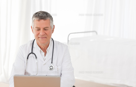 A senior doctor working on his laptop in his office FYI00483713