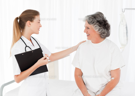 Nurse talking with her patient FYI00483714