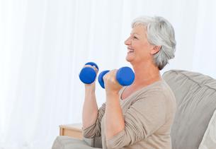 Senior doing her exercises on her sofa FYI00483721
