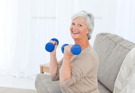 Senior doing her exercises on her sofa FYI00483723