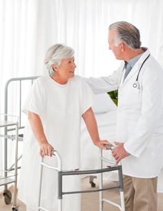 Doctor helping his patient to walk FYI00483814
