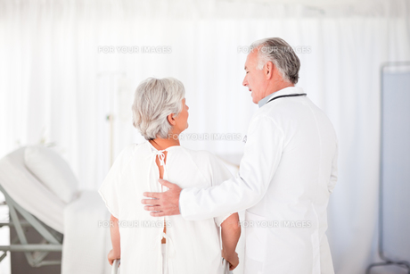 Doctor helping his patient to walk FYI00483818