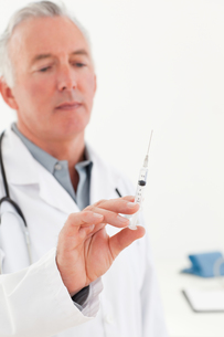 Senior doctor with syringes FYI00483828