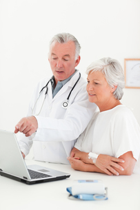Doctor and his patient looking at the laptop FYI00483832