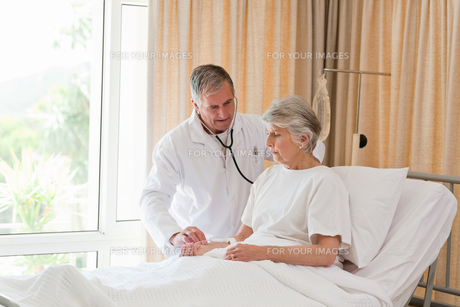 Senior doctor taking the heartbeat of his patient FYI00483837
