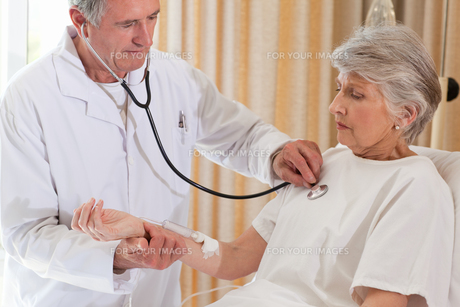 Senior doctor taking the heartbeat of his patient FYI00483838