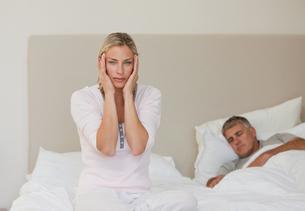 Woman having a headache while her husband is sleeping FYI00483858