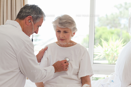 Senior doctor taking the heartbeat of his patient FYI00483874
