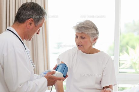 Doctor taking the blood pressure of his patient FYI00483876