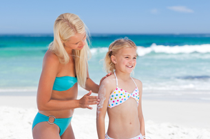 Mother applying sun cream on her daughter FYI00484072