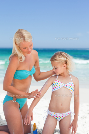 Mother applying sun cream on her daughter FYI00484073