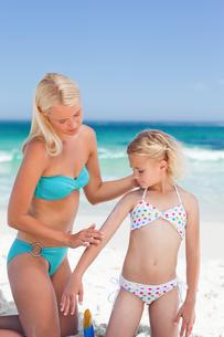 Mother applying sun cream on her daughter FYI00484073