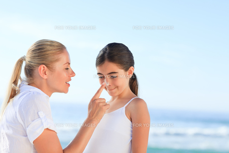 Mother applying sun cream on her daughter FYI00484125
