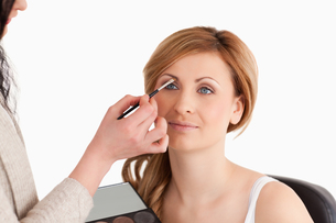 Makeup artist applying make up to a woman FYI00484225