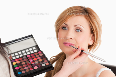 Pretty woman being made up by a make up artist FYI00484227