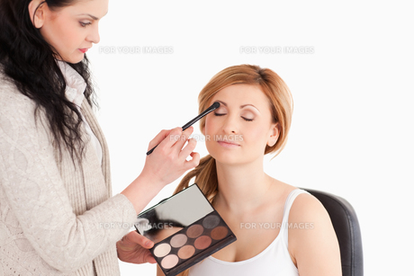 Young woman being made up by a makeup artist FYI00484228