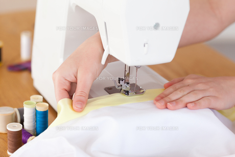 Caucasian hands using a sewing machine FYI00484368