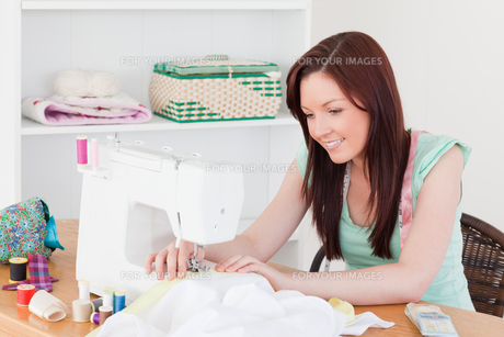 Pretty redhaired female using a sewing machine FYI00484370
