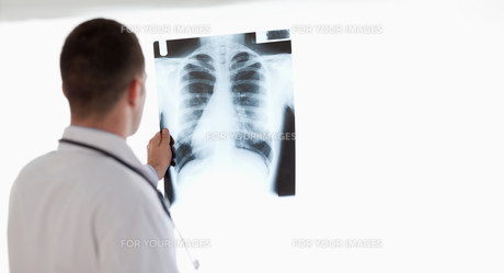 Doctor having a close look at xray while holding it against lightの素材 [FYI00484737]