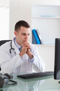 Doctor looking at computer screen FYI00484738