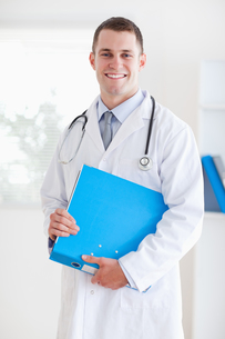 Smiling doctor with folder FYI00484739