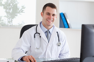 Smiling doctor on his computer FYI00484742
