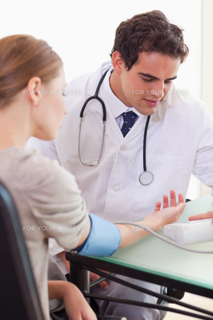 Doctor measuring his patients blood pressure FYI00484801