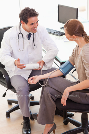 Doctor is relieved after taking his patients blood pressure FYI00484808