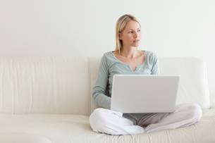 Woman sitting cross legged on the couch with her laptop FYI00484840