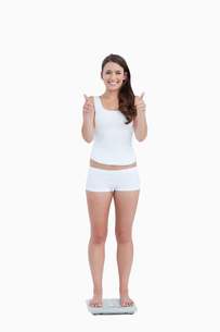 Smiling woman with her thumbs up while standing on weighing scales FYI00484997