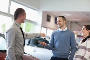 Salesman giving car keys to a coupleの素材 [FYI00485177]