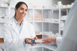 Smiling pharmacist giving a box to a doctor FYI00485269