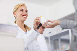 Pharmacist giving a drug box to a patient FYI00485311