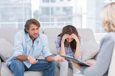 Young couple sit on the couch of the therapist FYI00485440