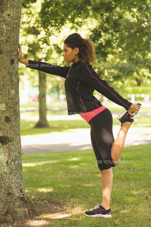 Healthy woman stretching her leg during exercise at park FYI00485608