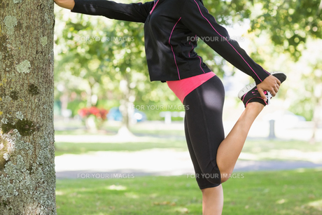 Side view of a woman stretching her leg during exercise at park FYI00485611